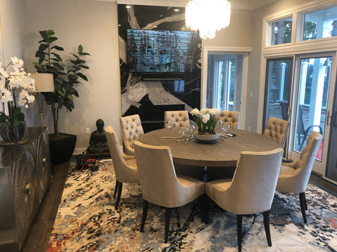 Dining room scene with round table, chairs, and a buffet.