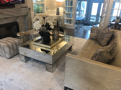 alternate angle of living room scene with grey tufted sofa, coffee table, and decor.