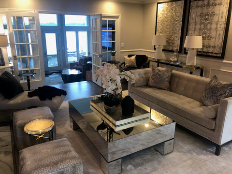 living room scene with grey tufted sofa, coffee table, and decor.