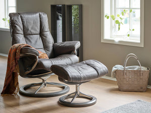 STRESSLESS LEATHER RECLINER CHAIR AND OTTOMAN WITH BLANKET DRAPED OVER ARM