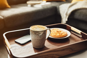 Mug of coffee, pastry and iPhone on a tray