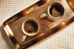2 cups of black Puccino's coffee sat on a copper coffee tray