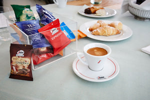 Collection of Segafredo Coffee Capsules next to mug of coffee and pastries