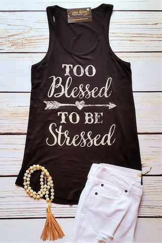 View of a black tank top that says Too Blessed To Be Stressed in white with white jeans and a chunky beaded tassel necklace