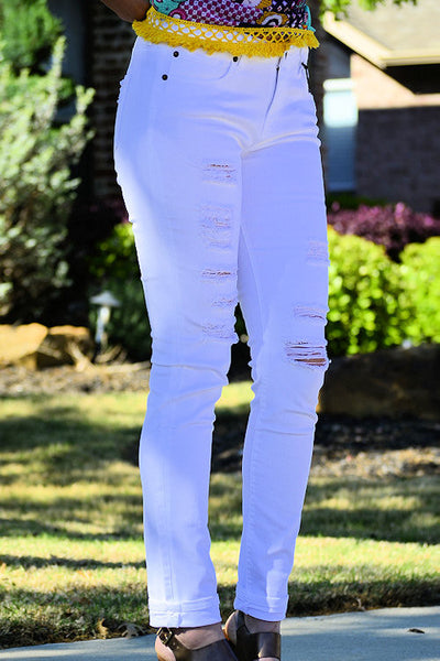 Side angle view of woman wearing ripped white skinny jeans