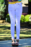 Front view of woman wearing ripped white skinny jeans