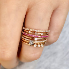 baguette and round halfway band capping off a stack of liven rings