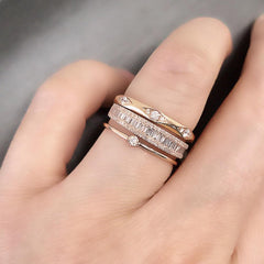 Heirloom baguette and round diamond halfway band worn as part of a stack with other Liven bands