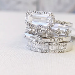 east-west emerald cut colored stone rings in a stack