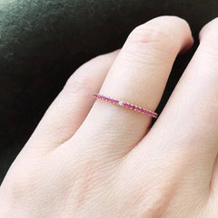 Ruby eternity band with diamonds at compass points on hand