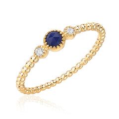 lapis lazouli center stone bracketed with diamonds on a 14k gold beaded band