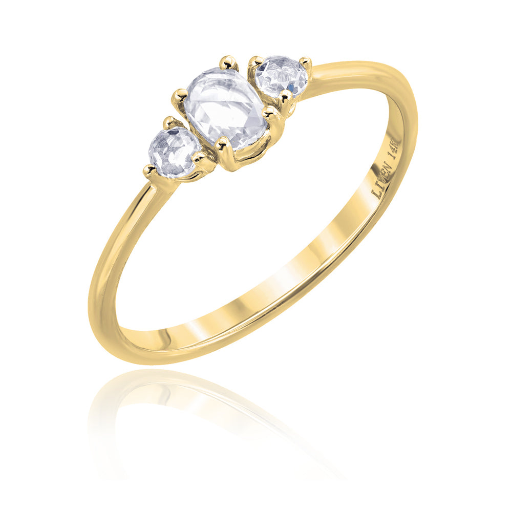 three rose cut diamonds on a yellow gold band. Center stone is oval, and 2 round side stones