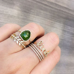 selection of yellow gold rings with a beautiful green ring centerpiece