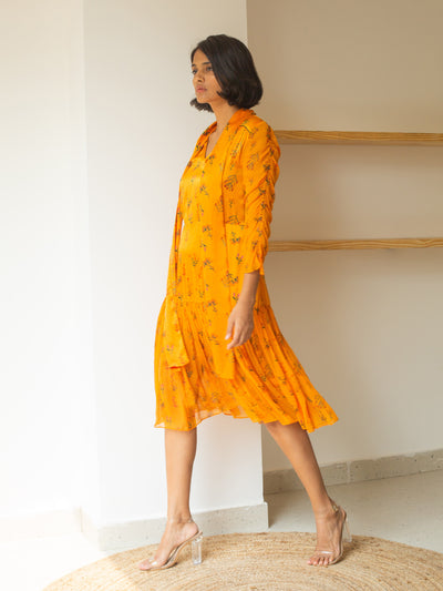 Girl wearing a flowy bright orange Pinar midi dress with floral print made of chiffon. The dress has an attached scarf. Concealed zipper on the side. Sheer chiffon full sleeves with ruching detail. Sheer chiffon on the hem layer.