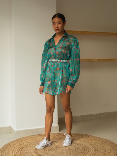 Girl in teal coloured mini shirt dress with white keds. The shirt is made in shiny sheer organza in teal with unique floral print in earth tones. The print has dry flower, evil eye and spices as elements.The girl is also wearing an elasticised-belt.