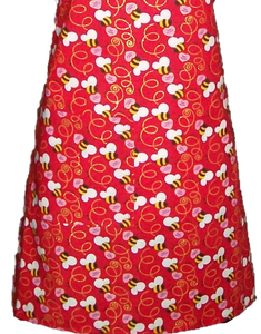 Red apron with bees and swirls and sweetheart candies with the words Bee Mine on it
