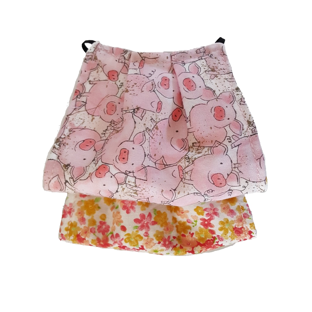 This is a newly handmade cotton adult fabric face cover. This is double ply, reusable and washable. Made in the USA   This can be used as a public courtesy cover.   **This is 1 face cover with a reversible pattern: Playful pigs scene on one side and Colorful flower buds on the other.
