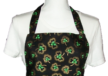 "Load image into Gallery viewer, This is a new handmade bib apron. The fabric is cotton. It is Black with Gold and Green Shamrocks on it. It has one right hand pocket. It measures approx. 27""-28"" from neck edge to bottom hem and 31.5"" from side to side. The bib is approx. 10.5"" wide. The neck strap is 20"" long total and the side ties are approx. 27""-28"" long. Nice gift for someone cooking your special meal, or you can just be cooking cute!"