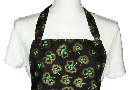This is a new handmade bib apron. The fabric is cotton. It is Black with Gold and Green Shamrocks on it. It has one right hand pocket. It measures approx. 27