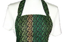 "Load image into Gallery viewer, This is a new handmade bib apron. The fabric is cotton. It is Black with 4 Leaf Clovers in different shades of Green and Gold on it. It has one right hand pocket. It measures approx. 27""-28"" from neck edge to bottom hem and 31.5"" from side to side. The bib is approx. 10.5"" wide. The neck strap is 20"" long total and the side ties are approx. 27""-28"" long. Nice gift for someone cooking your special meal, or you can just be cooking cute!"