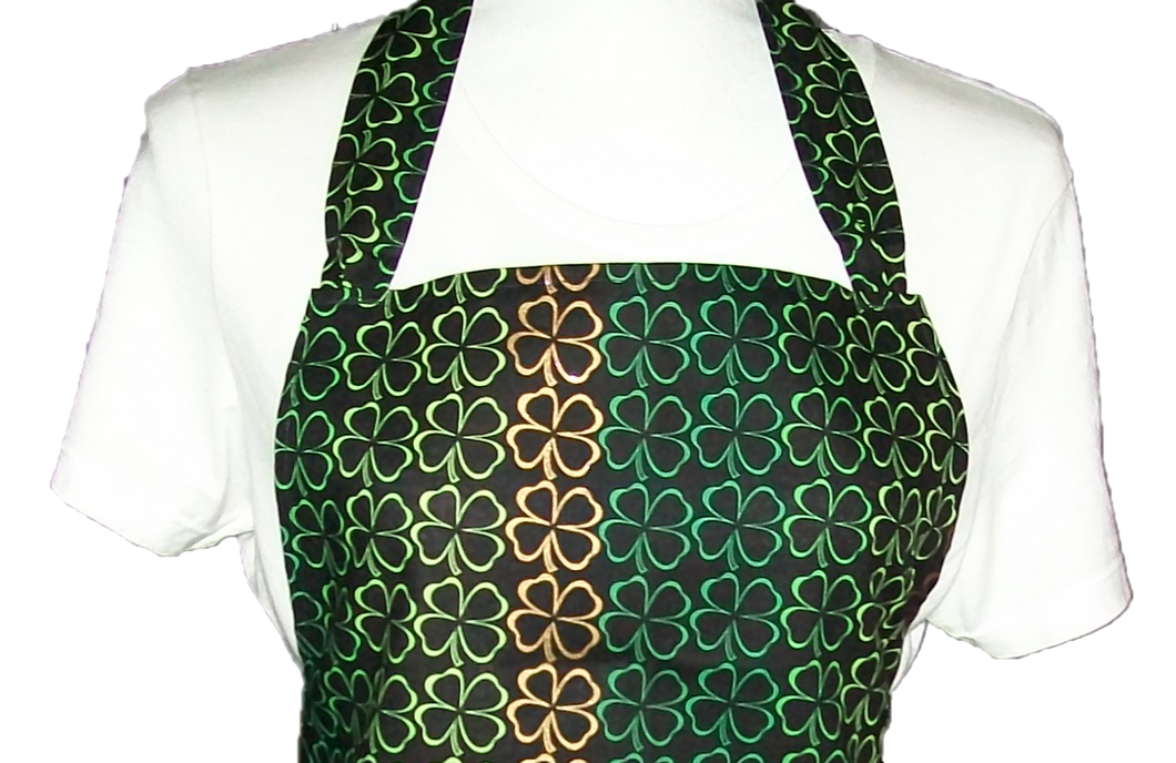 This is a new handmade bib apron. The fabric is cotton. It is Black with 4 Leaf Clovers in different shades of Green and Gold on it. It has one right hand pocket. It measures approx. 27