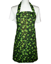 "Load image into Gallery viewer, This is a new handmade bib apron. The fabric is cotton. It is Black with Green 4 Leaf Clovers and Gold Sparkles on it. It has one right hand pocket. It measures approx. 27""-28"" from neck edge to bottom hem and 31.5"" from side to side. The bib is approx. 10.5"" wide. The neck strap is 20"" long total and the side ties are approx. 27""-28"" long. Nice gift for someone cooking your special meal, or you can just be cooking cute!  Note - This Apron has sparkles on it that may rub off, not suitable for food service"