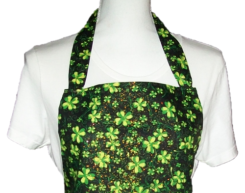 This is a new handmade bib apron. The fabric is cotton. It is Black with Green 4 Leaf Clovers and Gold Sparkles on it. It has one right hand pocket. It measures approx. 27