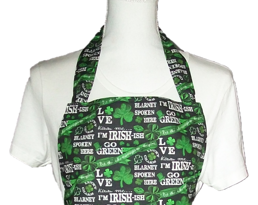 This is a new handmade bib apron. The fabric is cotton. It is Black with Green Shamrocks, 4 Leaf Clovers, and various Sayings on it such as