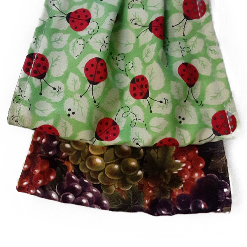 This is 1 face cover with a reversible pattern: Ladybugs on one side and grapes on the other