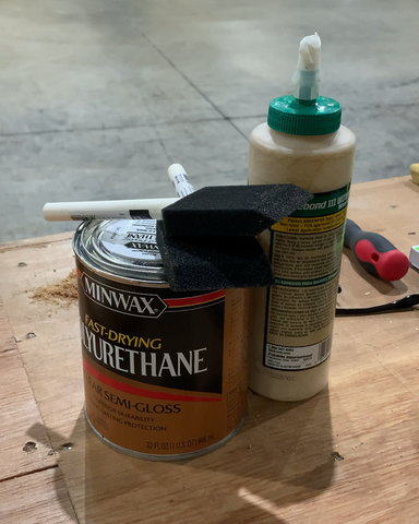Woodworking materials in wood workshop including Titebond III wood glue and polyurethane as well as wood finish brushes