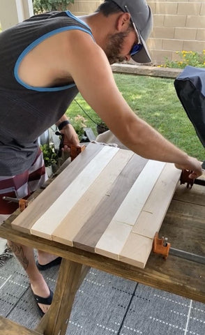 Woodworker wiping up wood glue on Forest 2 Home DIY cutting board in woodworking workshop