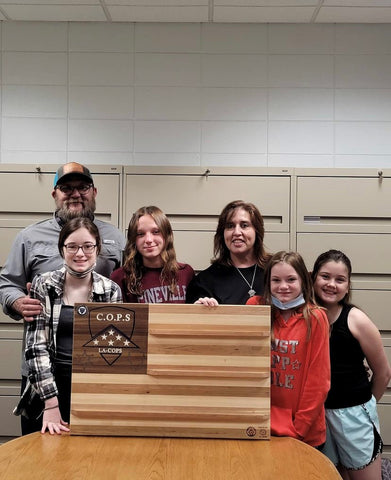 Annalee and the Johnson family with a woodworking project of a wood flag coin charger donated to the Louisiana Chapter of Concerns For Police Survivors Orgganization