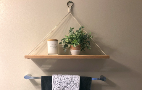 Completed macramé and Cherry hardwood hanging shelf adorned with a candle and potted plant for the perfect bathroom decor