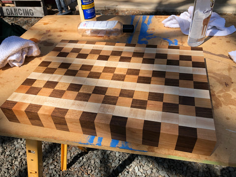 Cutting board with a patterned design, made of Hard Maple, Cherry and Walnut Wood. The cutting board is in a Wood Workshop/Woodworking Shop and is completed.