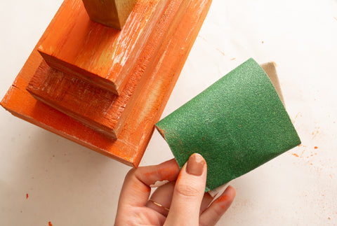 Female woodworker holding sandpaper to be used on painted woodworking project. Wooden pumpkin fall home decor being sanded with sandpaper to remove excess paint for a rustic farmhouse look