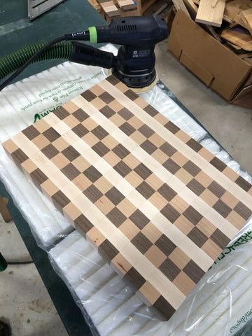 Patterned cutting board being sanded down. Cutting board is made with high quality lumber and wood. Wood species include Walnut, Hard Maple and Cherry Wood.