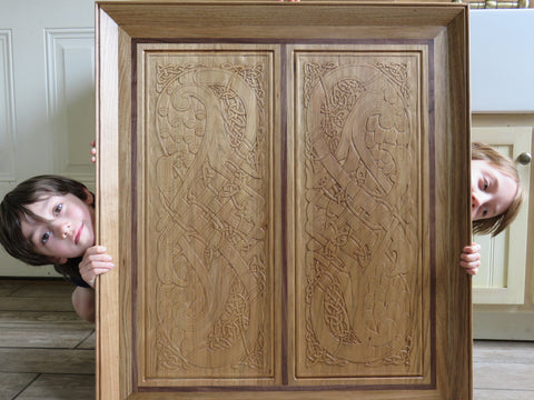 Children hiding behind a wood carving done by woodworker with Forest 2 Home premium hardwood lumber