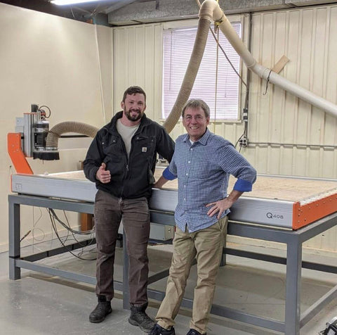 Forest 2 Home community member and veteran woodworker, Mike, standing next to large CNC machine for woodworking. Scroll saw projects, CNC projects, wooden signs