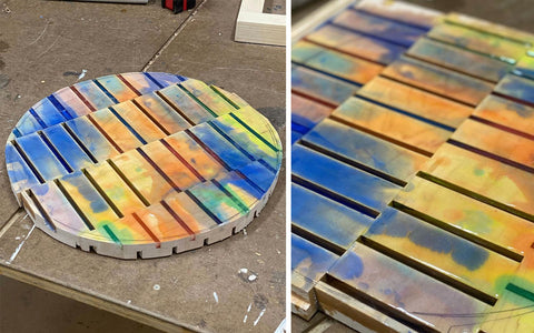 Colorful, rainbow epoxy resin pour over on a hardwood table top