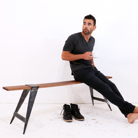 Woodworker, builder, maker and carpenter Ben Uyeda sits atop his mid-century modern modular bench. Crafted with welded steel and premium quality hardwood lumber in Walnut species