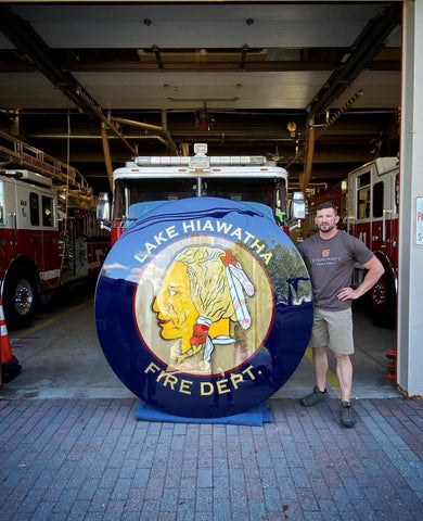 CNC machine sign made by woodworker in woodworking shop for fire house. Wood sign with logo displayed