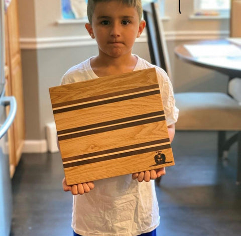 Young woodworker holding a custom cutting board kit made from Forest 2 Home premium quality hardwood cutting board kits