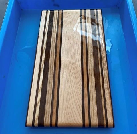 Oil wood finish being applied to Forest 2 Home premium hardwood cutting board made with Hard Maple wood, Walnut wood and Cherry wood
