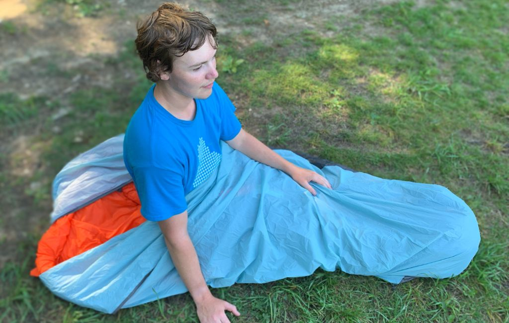 young individual inside a best ultralight bivy sack