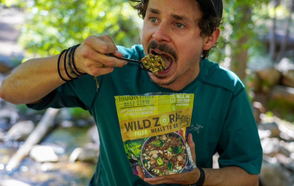 backpacker eating a freeze dried meal