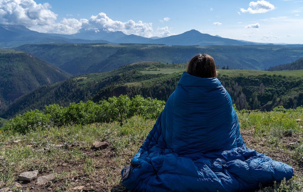 Female hiker wrapped in an unzipped quilt
