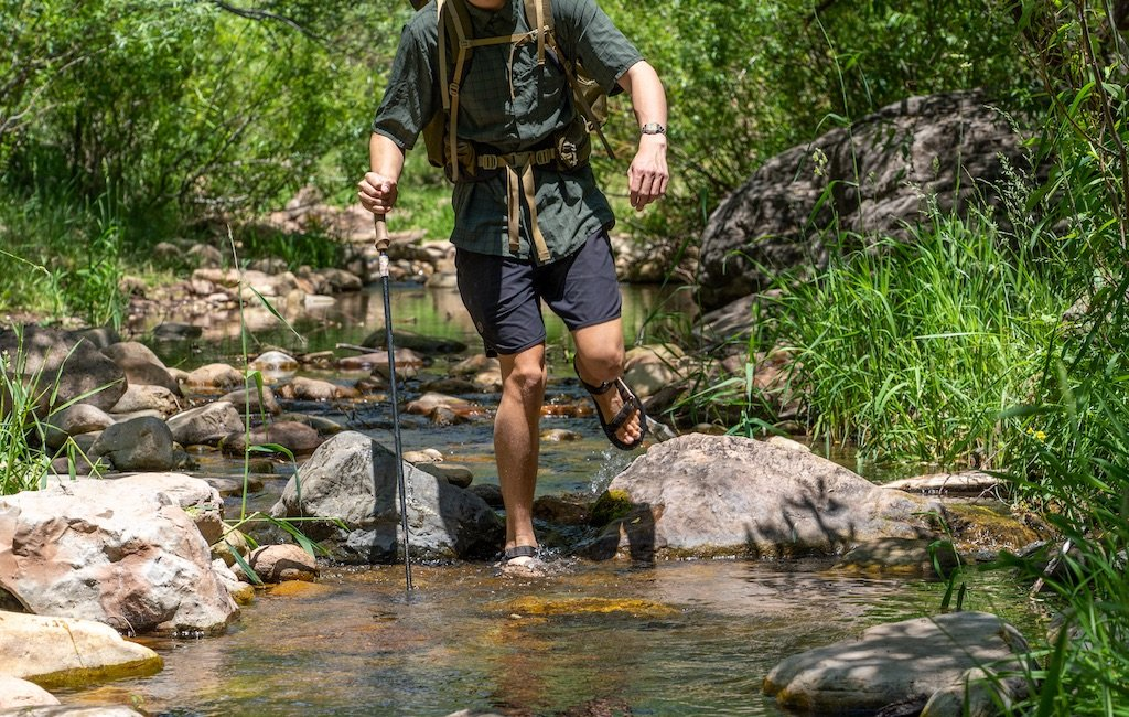 hiker crossing a river in hiking sandals