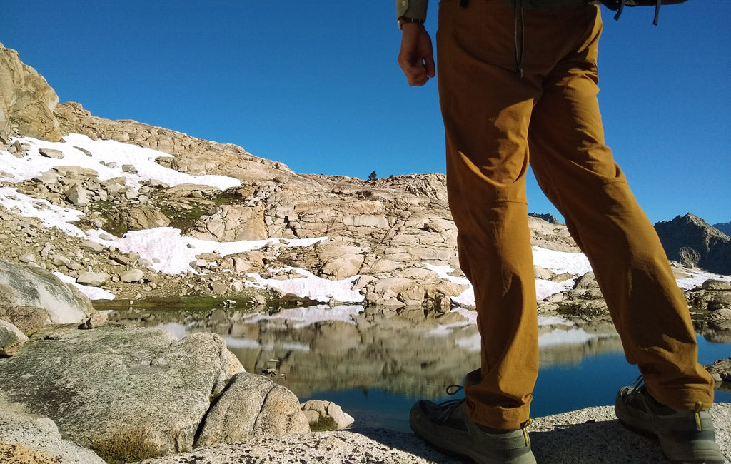 hiker wearing hiking pants in front of lake