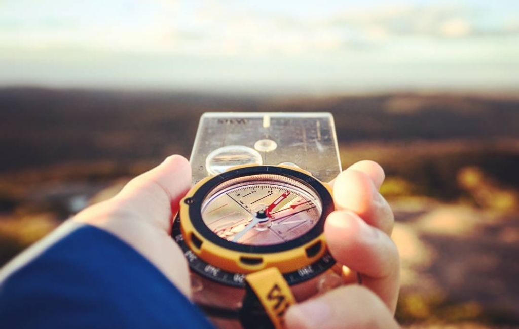 man using a compass to find hiking direction