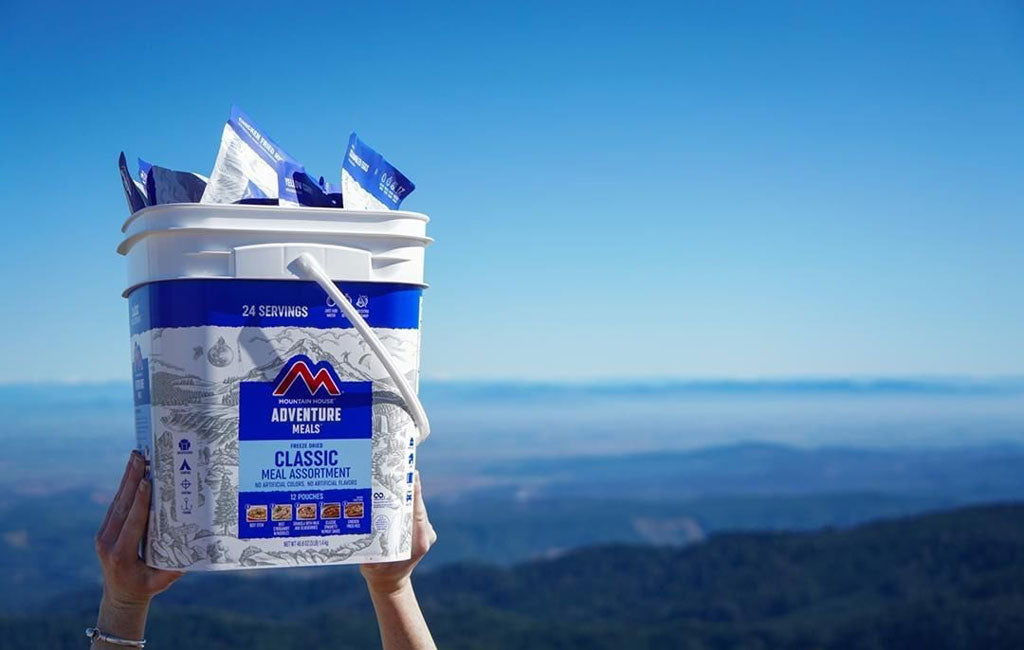 survival food bucket being held on mountain background